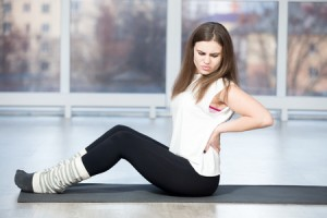 49572319 - portrait of injured unhappy fit young beautiful woman sitting in sports club, touching her back after working out in class, suffering from backache, feeling pain, full length, side view