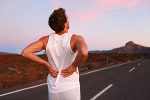 26496363 - back pain. athletic running man with injury in sportswear rubbing touching lower back muscles standing on road outside at night.