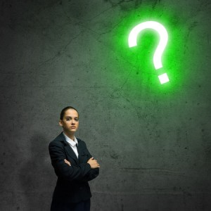 30722815 - young businesswoman looking thoughtfully at question mark