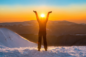 39704535 - woman on the top of winter mountain holding sun in her hands