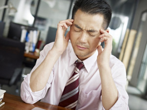44955125 - asian businessman having a headache in office.